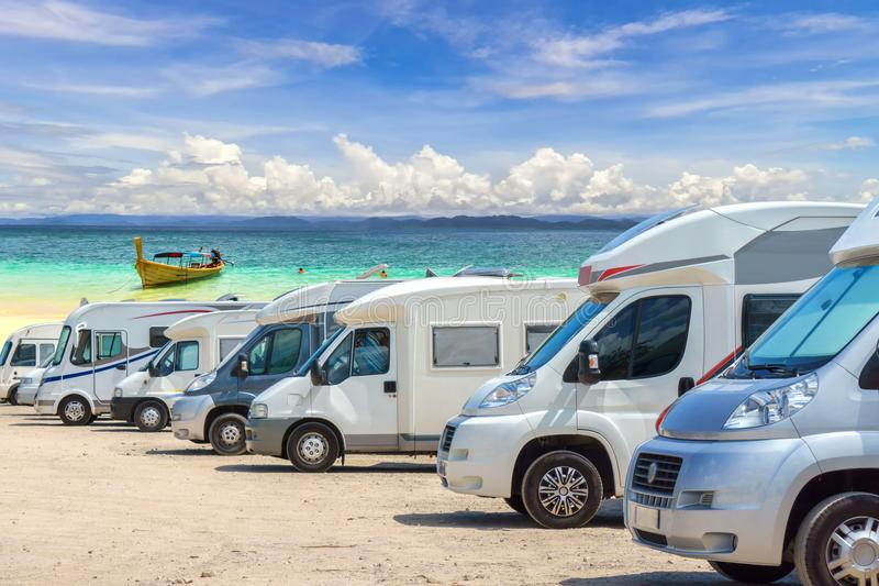 Close up motorhomes parked in a row on white sand beach and blue sky background. Thailand royalty free stock images