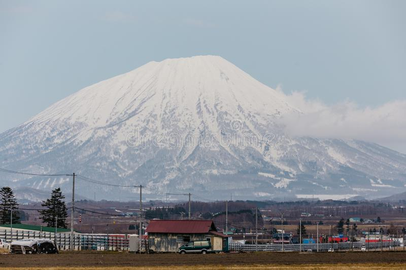 Close up Mount Yotei inactive stratovolcano with village on the foot hill and yellow grass on the ground in winter in Hokkaido. Japan royalty free stock photo
