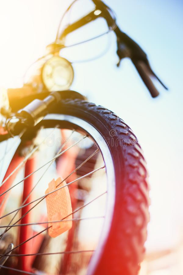 Close up of mountain bike tyres outside, summer day, city mobility. Bike in blurry background. Close up picture of a mountain bike tyre, summer day. Bike in the stock photos