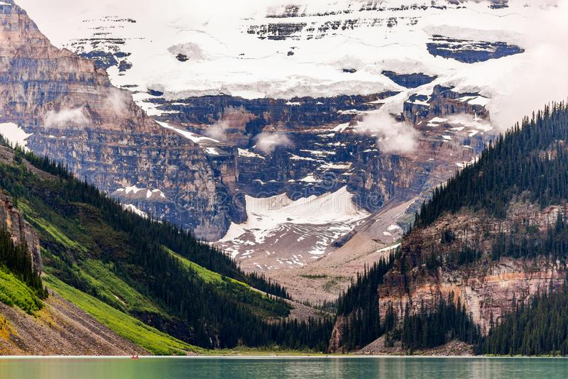 Close up of Mountain at Lake Louise. Framed by trees with reflection in water in Canada royalty free stock images