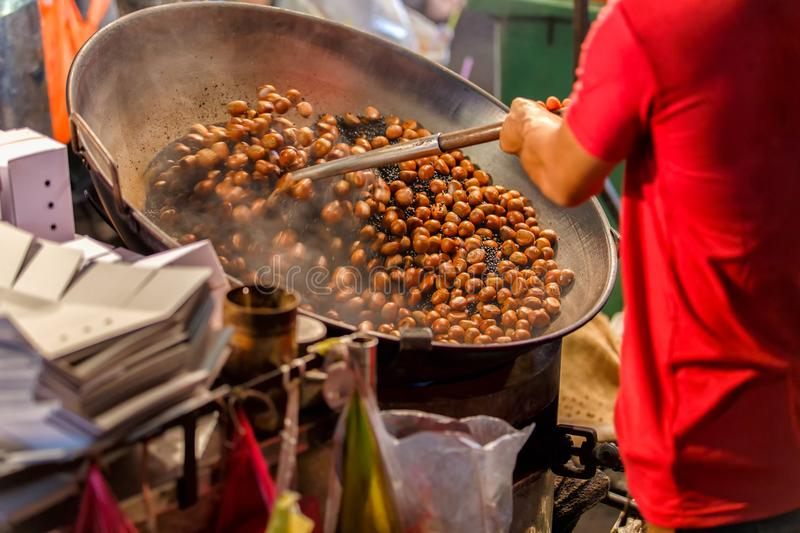 Close up movement hand a man worker roasting chestnuts in street chinatown or Yaowarat Road in Bangkok royalty free stock image