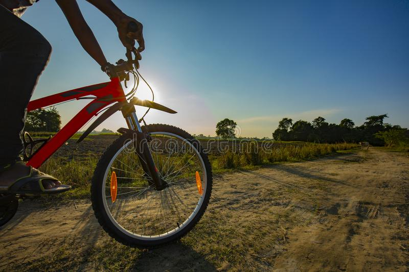Close up of a moving bicycle from village mud road on a evening day royalty free stock photos