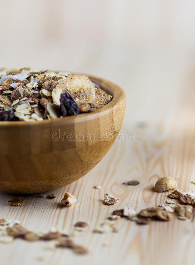 Close-up of Muesli and granola in blurred wooden background. (Shallow aperture intended for the aesthetic quality of the blur). Close-up of Muesli and granola in royalty free stock photo