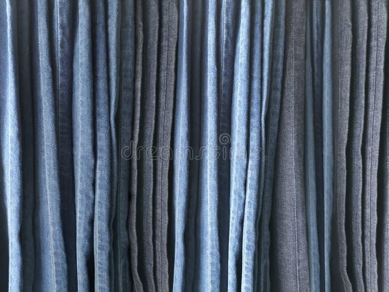 Close up muitas calças de brim que penduram em uma cremalheira Fileira das calças de brim da sarja de Nimes das calças que pendur imagem de stock royalty free