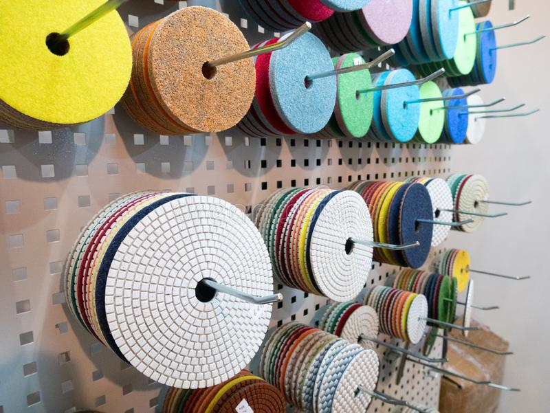 Close up muito discos substituíveis de lustro e de moedura diferentes para as ferramentas elétricas industriais que penduram no imagem de stock royalty free