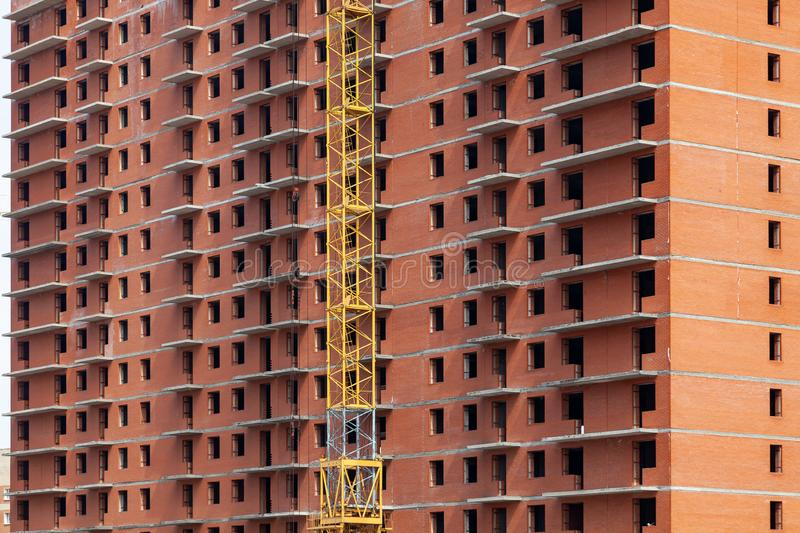 Close-up on a multi-storey residential building under construction from red brick with a part of a yellow crane. The walls of the. House in the process of work royalty free stock photos
