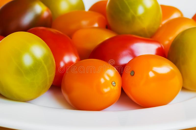 Close-up of multicolored cherry tomatoes on a white porcelain plate. Heap of yellow, orange and red small tasty tomatoes. stock photography