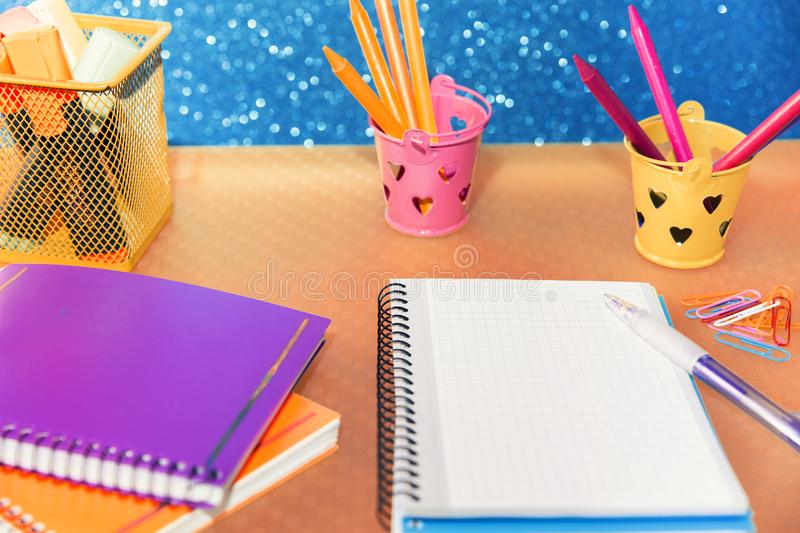 View of different containers with pencils and markers for drawing and writing in a blank notebook. Close-up of multicolored containers with pencils and markers stock images