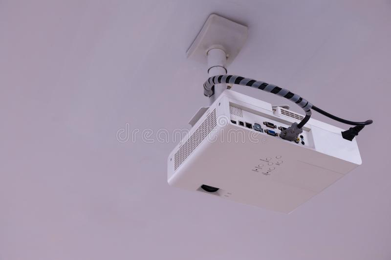 Close up Multimedia projector installed on the ceiling royalty free stock image