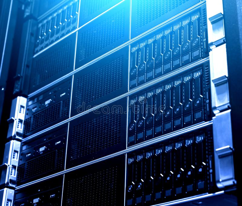 Close up multiple system of modern cloud storage data equipment under blue light. Technological rack inside. Technology and stock images