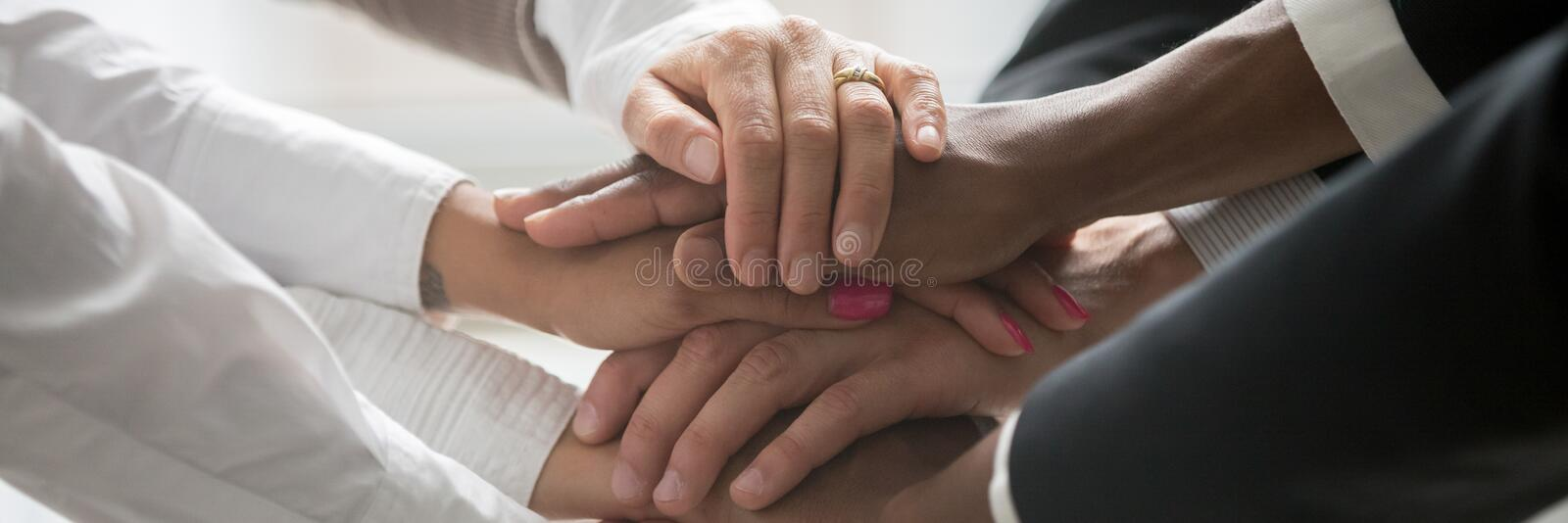 Multinational business people stack their hands together symbol of unity stock photo