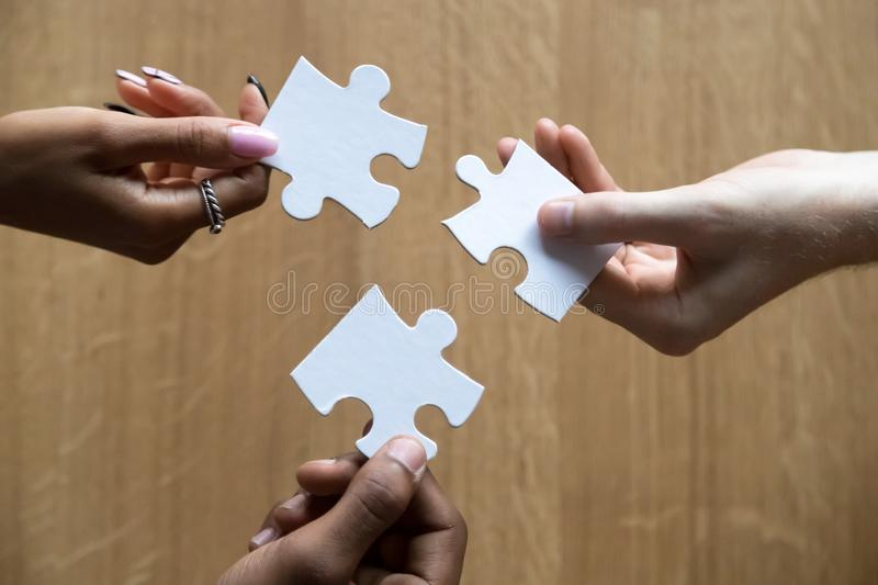 Close up of diverse people assemble jigsaw finding best solution royalty free stock photo