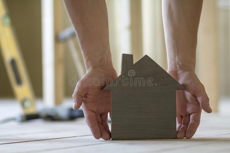 Close-up of muscular male hands holding small brown wooden model house on blurred background of building tools. Construction, inve royalty free stock images
