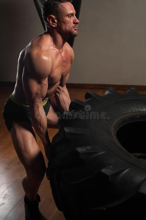 Close-up - muscular strong man lifting heavy tyre royalty free stock photo