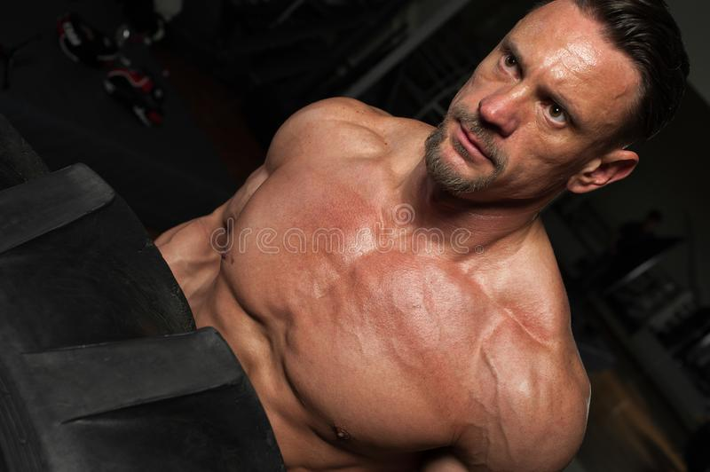 Close-up - muscular strong man lifting heavy tyre stock photography