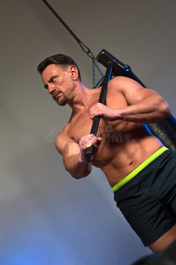 Close-up muscular strong man training with hammer royalty free stock image