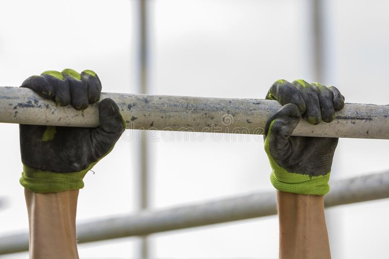 Close-up of muscular worker hands hanging on scaffold metal pipe on white house wall with polyurethane foam sheet background. Mode stock photography
