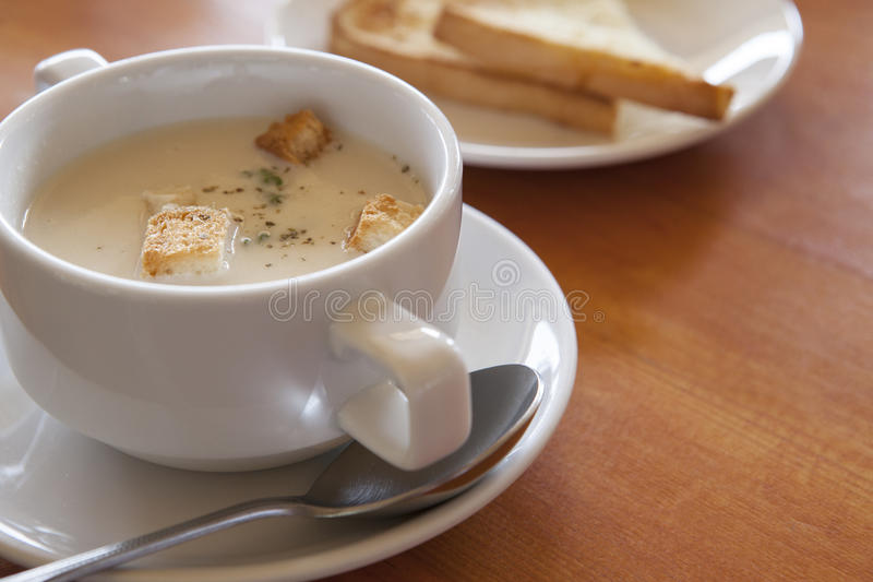 Close up of mushroom soup in white ceramic cup on table top. File of close up of mushroom soup in white ceramic cup on table top stock photo