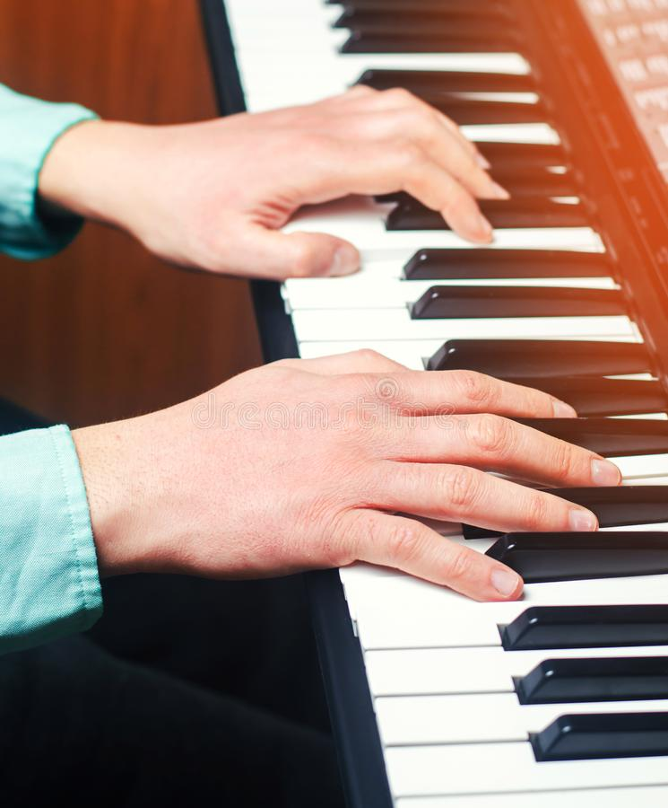 Close-up of a music performer`s hand playing the piano, man`s ha royalty free stock images