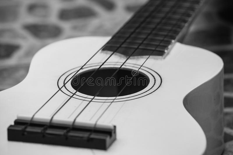 Close up of musical instrument ukulele guitar. Close up of musical instrument ukulele guitar on cement floor. Black and White filter effect stock photography