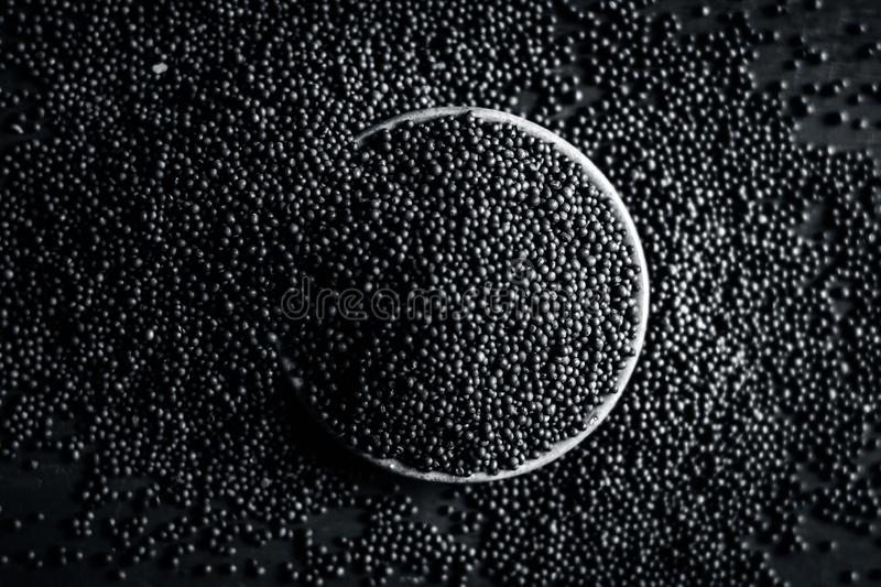 Close up of mustard seeds/Rai or brown mustard seeds in a small plate on a wooden surface in dark Gothic colors. stock images