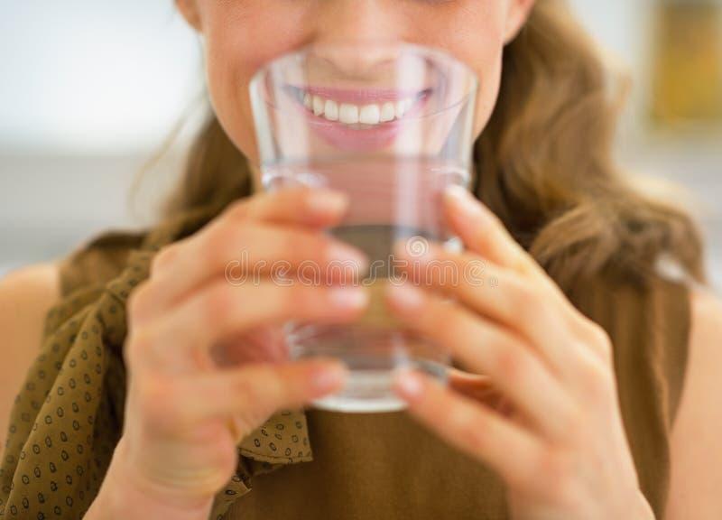 Close up na água potável nova da dona de casa foto de stock