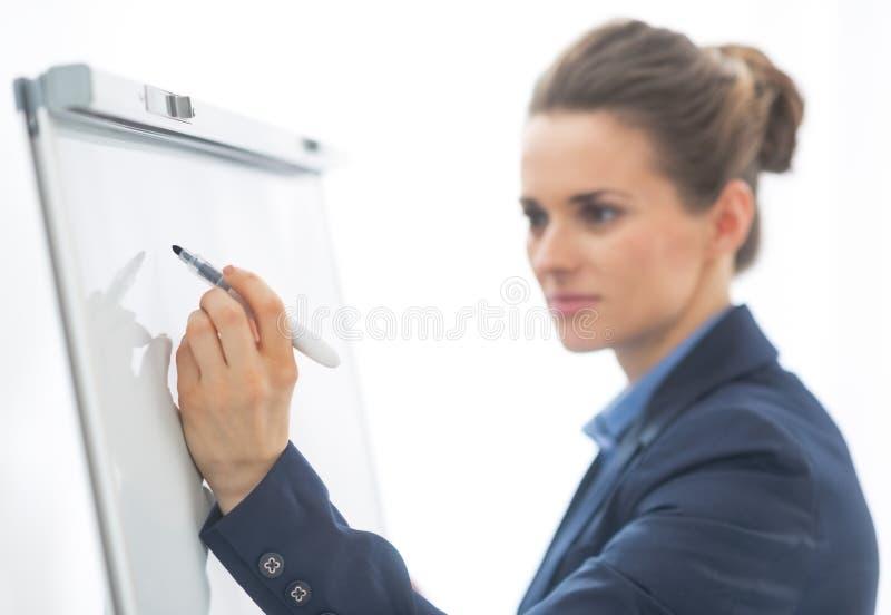 Close up na escrita da mulher de negócio no flipchart foto de stock royalty free