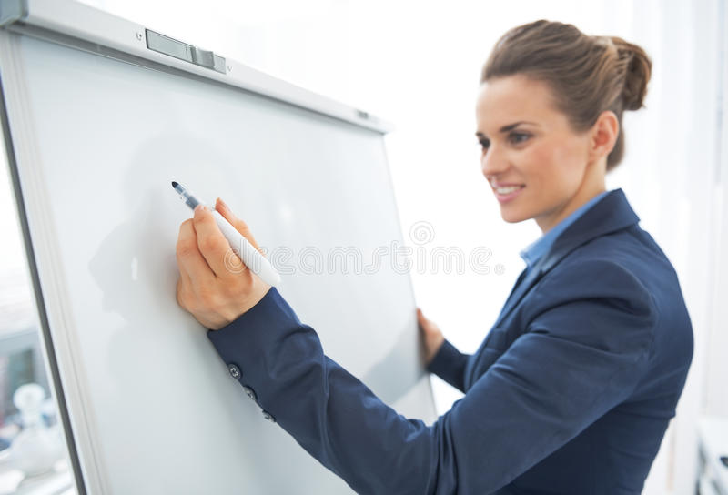 Close up na escrita da mulher de negócio no flipchart fotografia de stock royalty free