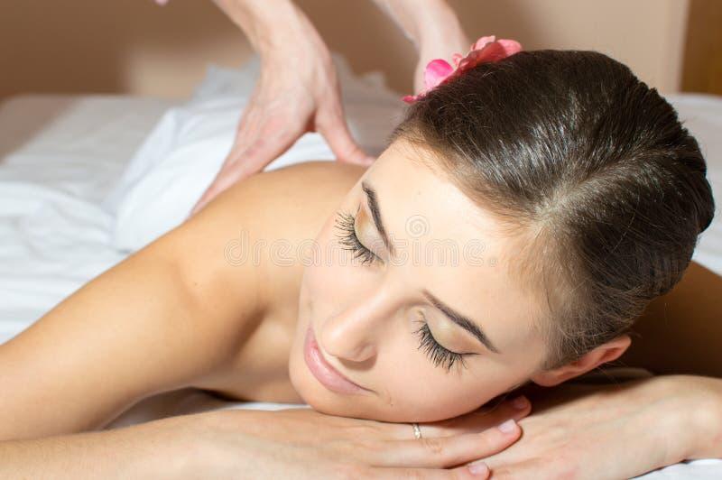 Close up na mulher bonita cansado que encontra-se em uma tabela e que tem o divertimento que toma massagens da beleza foto de stock