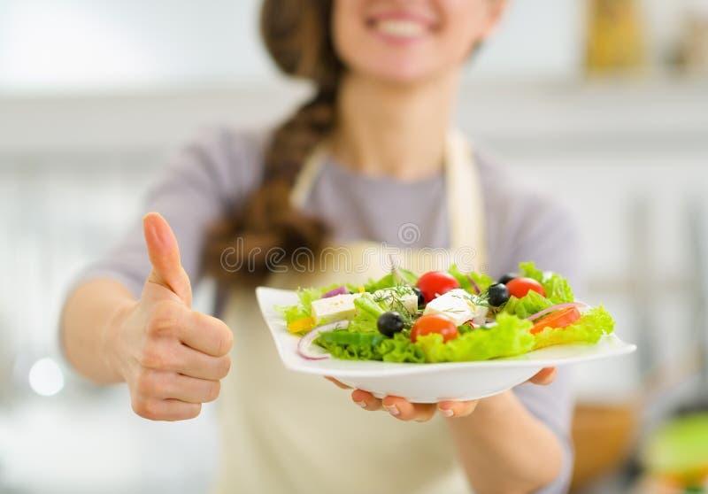 Close up na mulher que mostra a salada e os polegares frescos acima imagens de stock