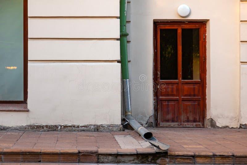Close-up na parede de uma construção velha com uma porta marrom de madeira com uma lâmpada para iluminar a entrada e uma tubulaçã fotografia de stock