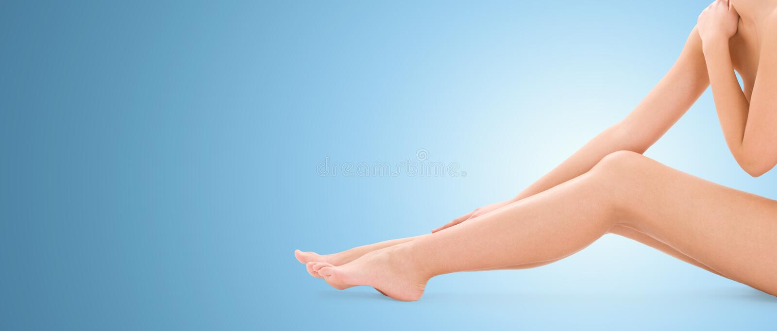 Close up of naked woman legs over blue background stock photo