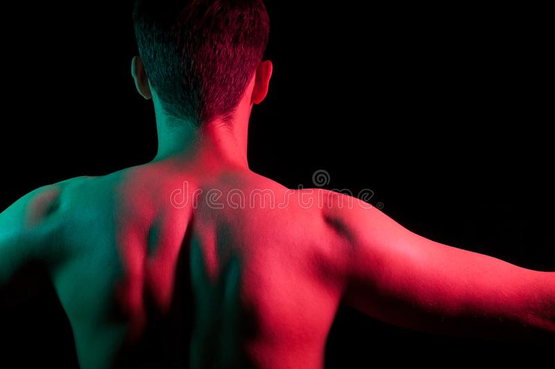 Close-up of nape, back and shoulders with strained muscles and hands apart of an short hair head of a man with stubble, naked stock photography