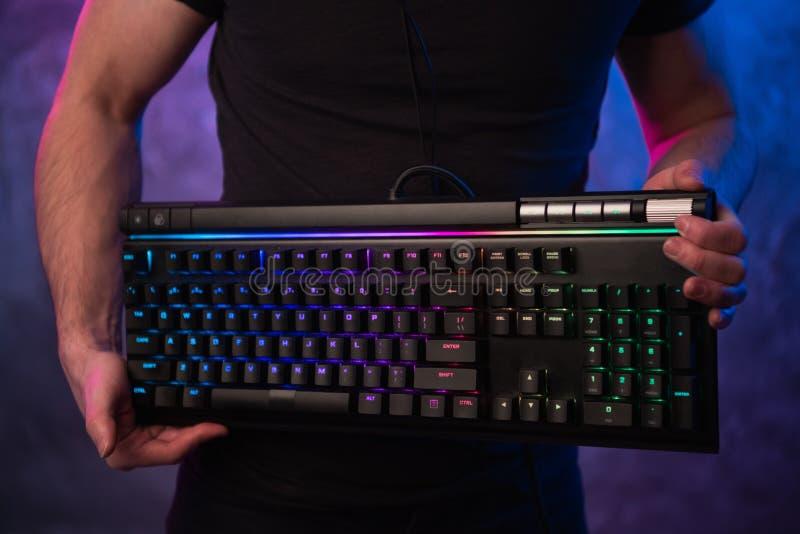Close-up nas mãos do gamer que guardam um teclado O fundo é Lit com luzes de néon fotografia de stock royalty free