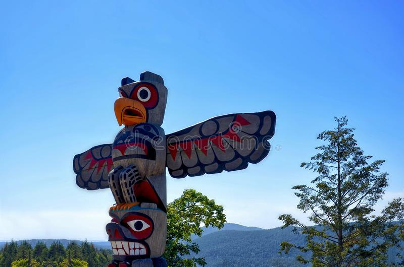 Close-up of native Americans totem on a background of the sea bay surrounded by mountains and coniferous forest. Cowichan Valley, Vancouver Island, Canada stock photo