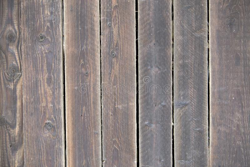 Close-up of natural old vintage weathered gray brown unpainted solid wooden fence or gate of planks and boards. Ecological texture royalty free stock photo