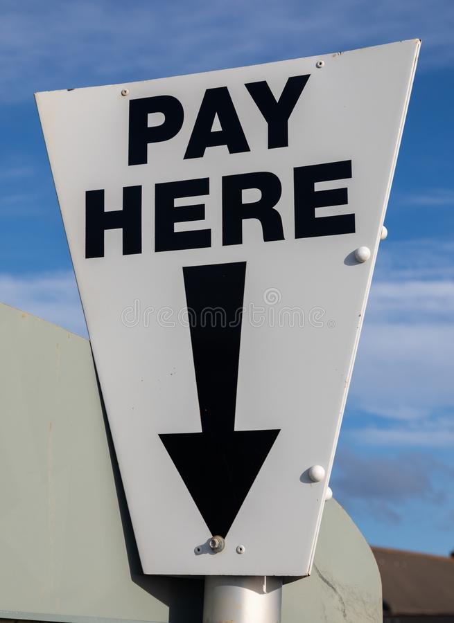 Close-up of a near triangular black and white pay here sign at a cark park St Annes on Sea Fylde Coast February 2019. Close-up of a near triangular black and stock image