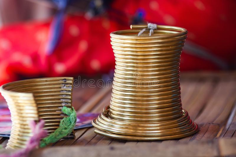close up on a neck ring worn by long neck karen women stock photo