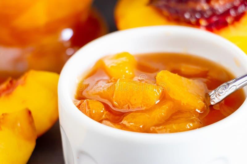 Close up Nectarine jam confiture in ramekin and jar. Dark background. Selective focus.  royalty free stock photography