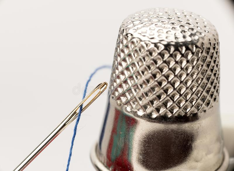 Close up of a needle threaded and a thimble macro stock photo