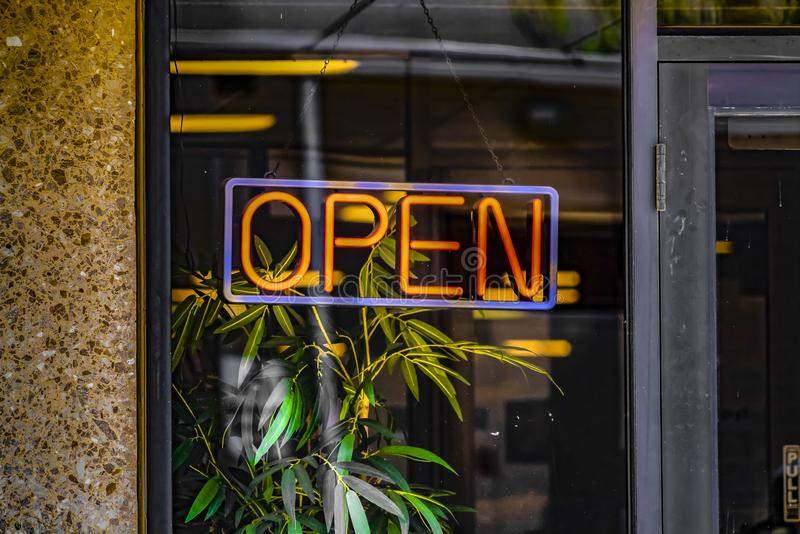 Close up of a neon open sign hanging on the glass wall of a commercial building royalty free stock photos