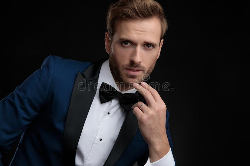 Close up of a nervous groom wearing a blue tuxedo. Close up of a nervous groom holding his hand in his chin while wearing a blue tuxedo and a black bowtie stock photos