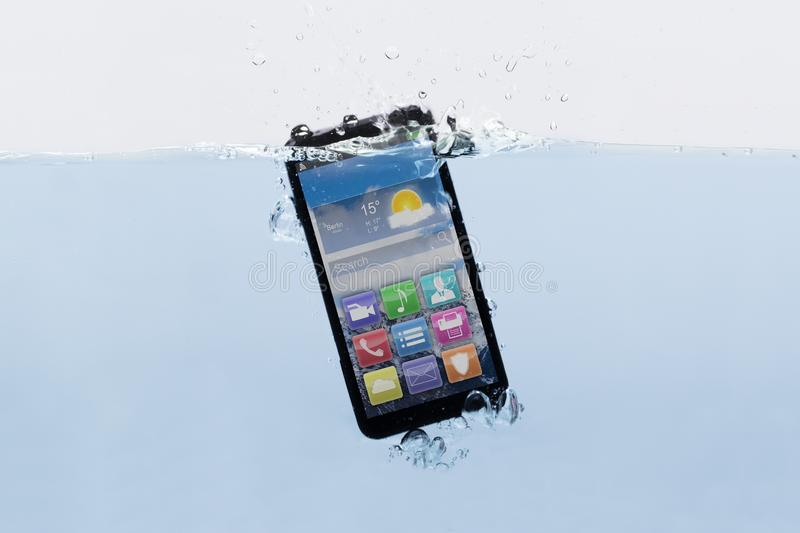 Mobile Phone Submerged In Water. Close-up Of A New Black Mobile Phone Submerged In Water stock photo
