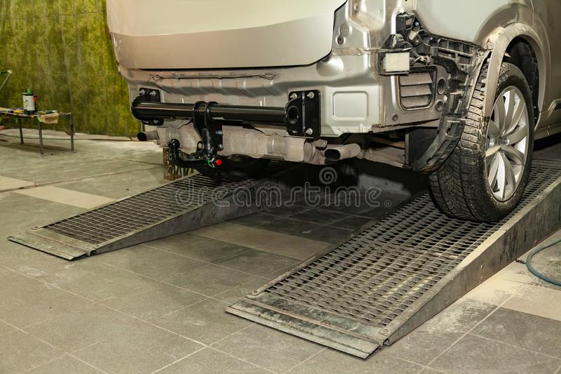 Close-up on a new black tow hitch installed on a modern car with a beige-colored bumper removed in a vehicle repair shop. The stock image