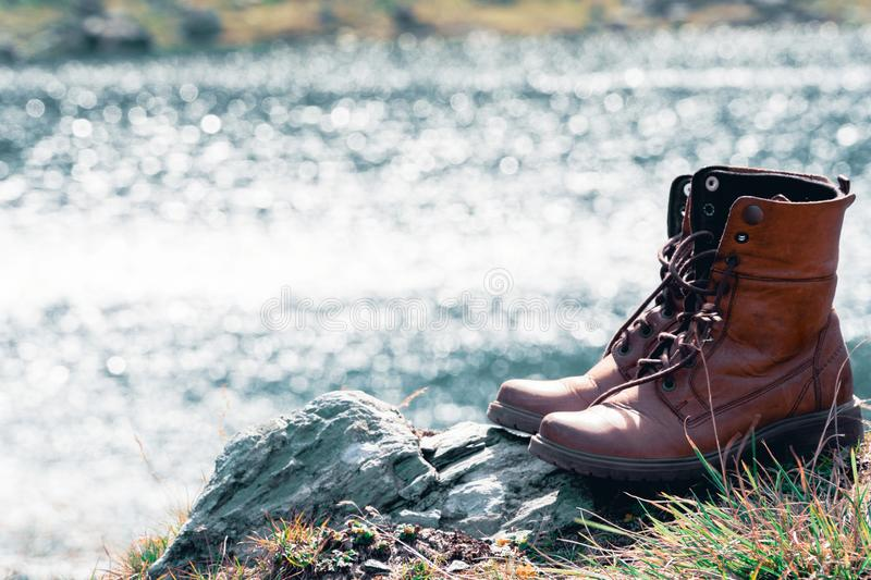 Close up new brown leather shoe on mountain lake view point. Adventure concept, hiker, travel. Copy space royalty free stock photo