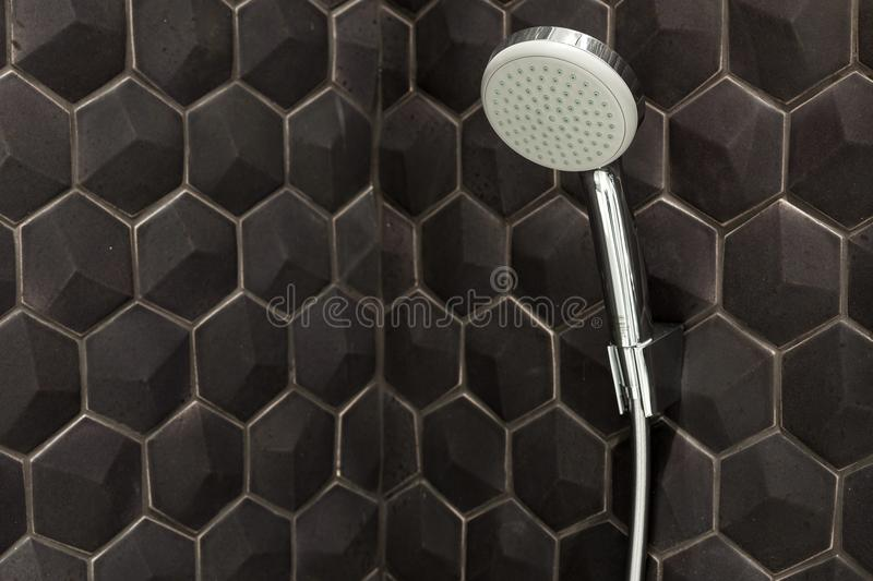 Close up of new rain shower head in the bathroom against a background of black tiles. royalty free stock photos