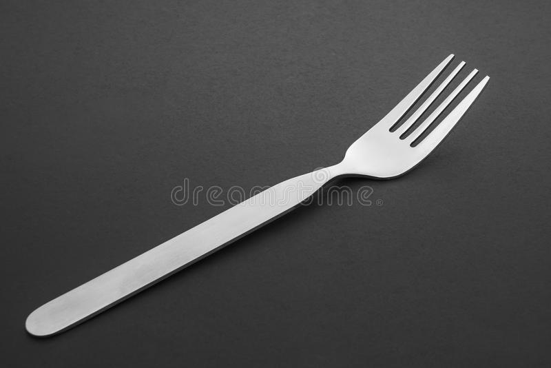 Close up new stainless steel kitchen fork on black table royalty free stock images