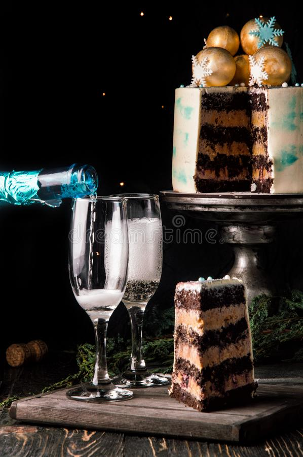 Close up. New Year celebration. Ð¡ake in the cut. Nearby is a wooden board with a piece of sliced chocolate cake and two glasses stock image