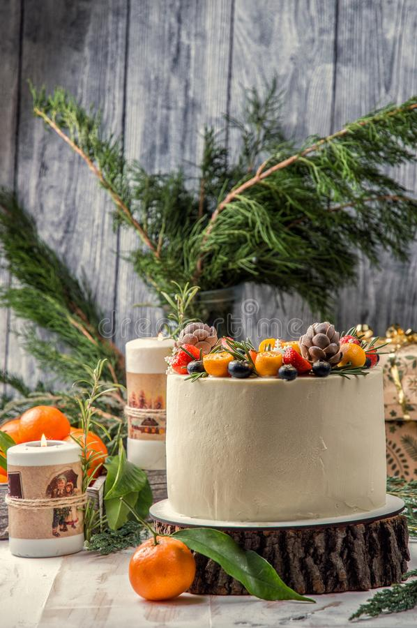 Close up. New Year`s Cake, decorated various berries. Nearby are orange tangerines, burning festive candles stock photo