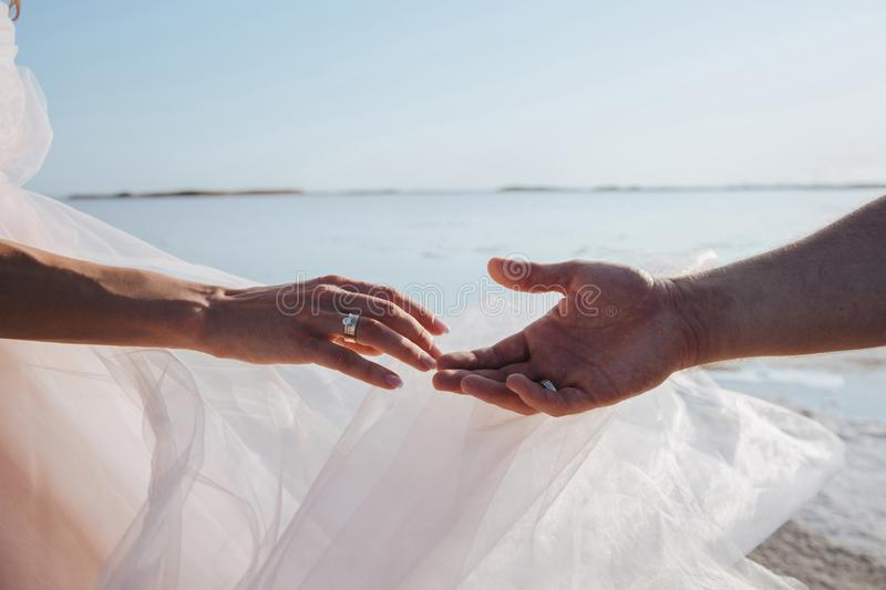 Close-up of newlywed loving couple holding hands on the beach. concept of love. stock photo